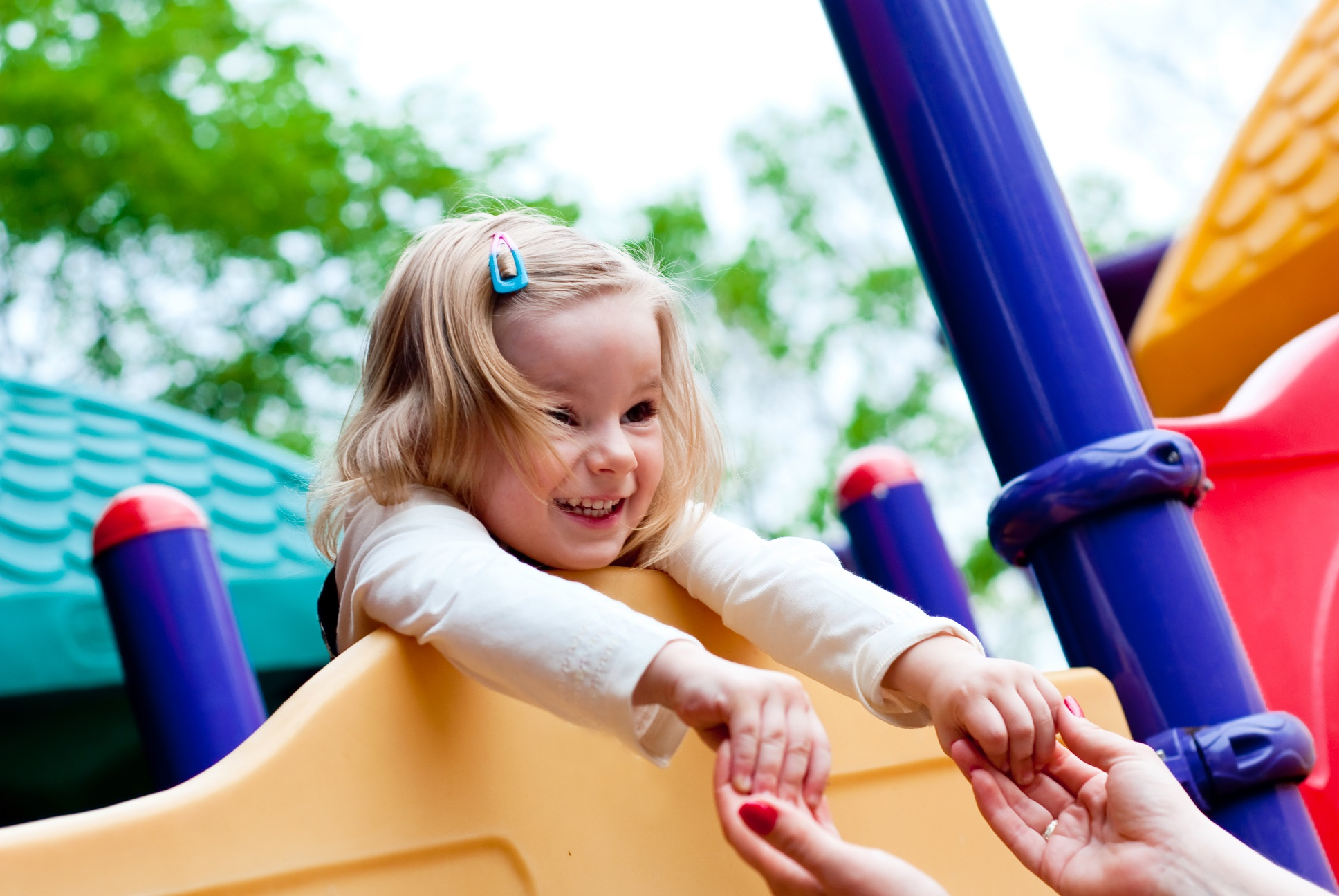 Little smiling girl in the playground.  Focus on face